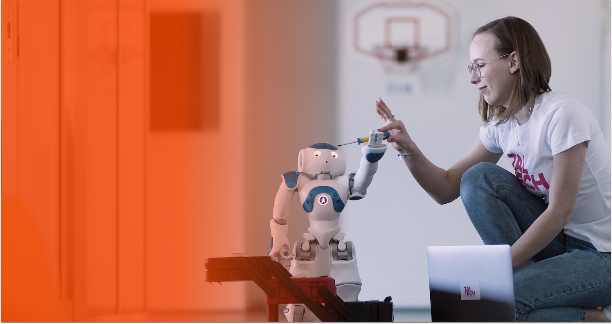 A womand and a small robot interacting.