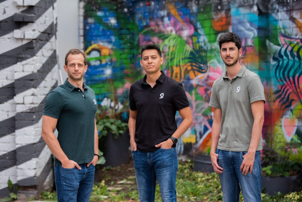 Three guys standing in front of a graffiti wall