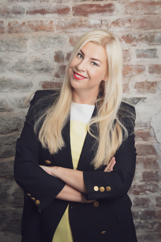Blond Estonian woman in front of a brick wall